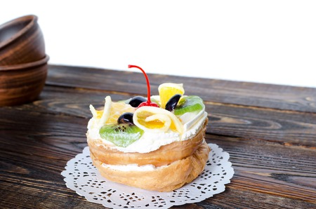 Choux pastry with cream and fruit on old table