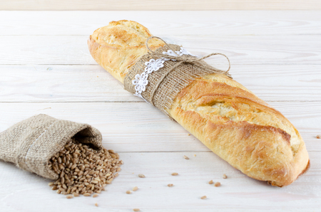 White baguette tied with burlap sack of wheat grains.