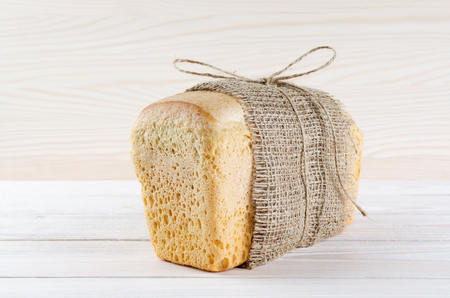 satisfying: A loaf of fresh white bread wrapped in burlap on a light wooden table.