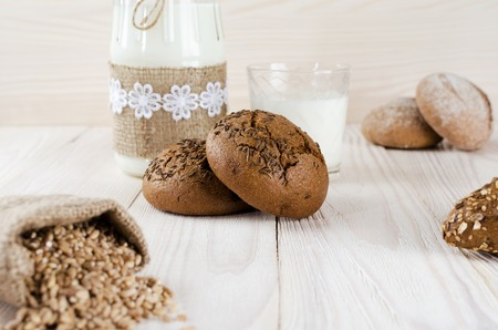 Brown rolls with caraway seeds on the table with milk in a jar. Wheat grains in the pouch.