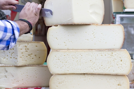 A stack of traditional, large Cretan graviera cheeses on display at a farmers