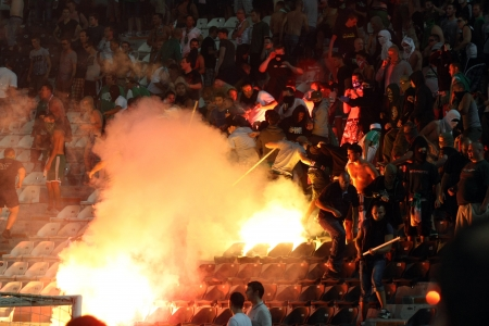 delirious: THESSALONIKI, GREECE-AUG 23, 2012:Clashes PAOK Thessaloniki and Rapid Vienna fans and the police before UEFA Europe League Playoff Football Match at Toumba Stadium