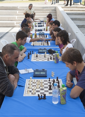 decs: THESSALONIKI,GREECE - OCT 07,2012:Unidentified players take part at chess tournament marathon of 30 rounds for beginners and experienced chess players in Thessaloniki