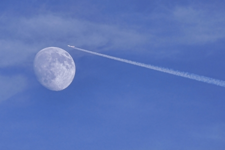 Jet stream of airplane going through the moon in blue sky Stock Photo - 16268370