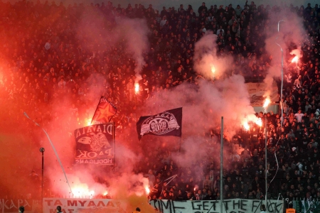 THESSALONIKI, GREECE - OCT 30, 2011: Fans and supporters of PAOK team light flares in football match between Paok and Panathinaikos cheering for their team goals