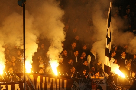 delirious: THESSALONIKI, GREECE - FEB 5, 2012: Fans and supporters of PAOK team light flares in football match between Paok and Olympiacos cheering for their team goals