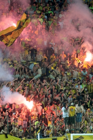 delirious: THESSALONIKI, GREECE - AUGUST 5 ,2009: Fans of Aris team light flares in football match between Aris and Boca Juniors cheering for their team goals