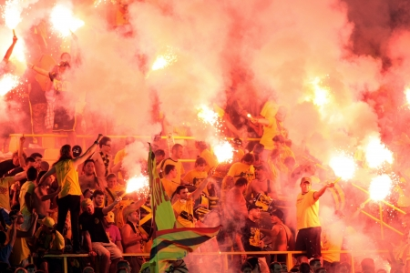 delirious: THESSALONIKI, GREECE - AUGUST 5, 2009: Fans of Aris team light flares in football match between Aris and Boca Juniors cheering for their team goals