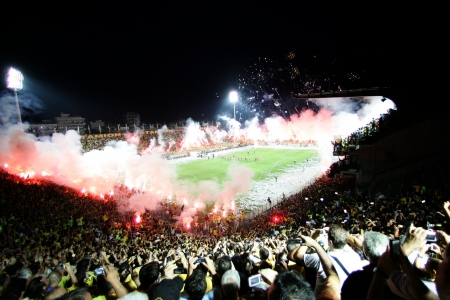 delirious: THESSALONIKI, GREECE - AUGUST 5, 2009: Fans and supporters of Aris team light flares in football match between Aris and Boca Juniors cheering for their team goals