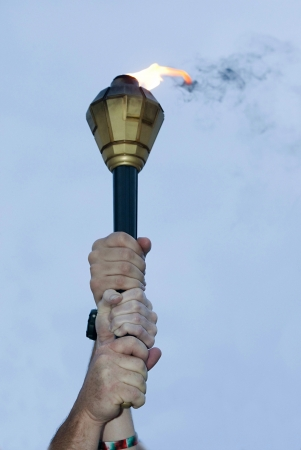 Three hands holding a flaming torch in the blue sky