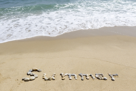 Word summer written in sand on the beach  photo