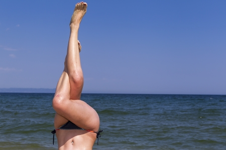 Woman doing yoga exercise on beach photo
