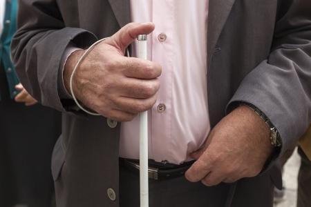 Close up in blinder Mann, seine Hände halten einen Stock