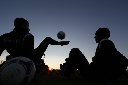 thessaloniki: THESSALONIKI, GREECE - JANUARY 3: Silhouettes of soccer players of PAOK Thessaloniki team during training background on the sunset sky at Mesimvria stadium on January 3, 2013 in Thessaloniki, Greece