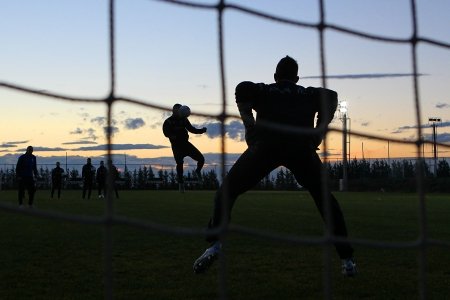 THESSALONIKI, GREECE - JANUARY 3: Silhouettes of soccer players of PAOK Thessaloniki team during training background on the sunset sky at Mesimvria stadium on January 3, 2013 in Thessaloniki, Greece