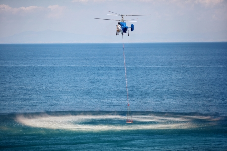 THESSALONIKI,GREECE - SEPT,8: Helicopter dipping its bucket to load water on September 08, 2013 in Thessaloniki, Greece.