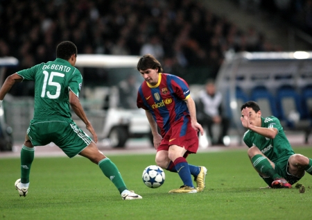ATHENS, GREECE - NOV 24 : Gilberto of Panathinaikos (L) in action with Messi of Barcelona (R) during the UEFA Champions League group stage match Panathinaikos vs Barcelona on November 24, 2010 in Athens, Greece
