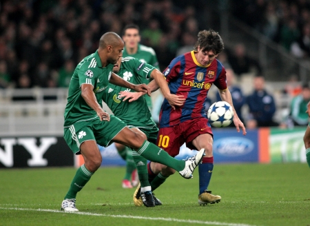 ATHENS, GREECE - NOV 24 : Boumsong of Panathinaikos (L) in action with Messi of Barcelona (R) during the UEFA Champions League group stage match Panathinaikos vs Barcelona on November 24, 2010 in Athens, Greece