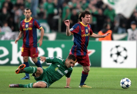 ATHENS, GREECE - NOV 24 : Katsouranis of Panathinaikos (L) in action with Messi of Barcelona (R) during the UEFA Champions League group stage match Panathinaikos vs Barcelona on November 24, 2010 in Athens, Greece