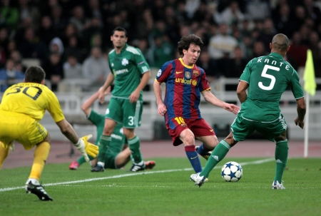 ATHENS, GREECE - NOV 24 : Kante of Panathinaikos (R) in action with Messi of Barcelona (L) during the UEFA Champions League group stage match Panathinaikos vs Barcelona on November 24, 2010 in Athens, Greece