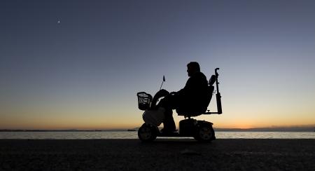 Silhouette einer Person mit Behinderungen auf Rollstuhl auf den Sonnenuntergang