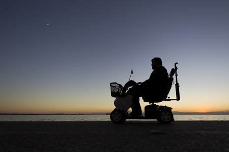 silhouette of a person with disabilities on wheelchair on the sunset