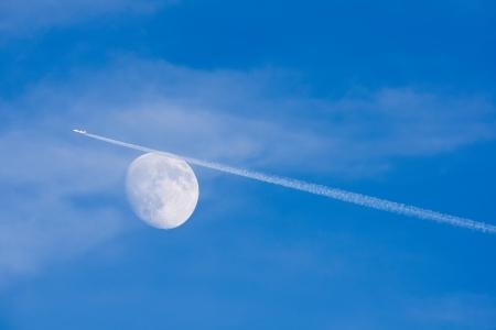 jet stream: Corriente en chorro de avi�n pasando por la luna en el cielo azul