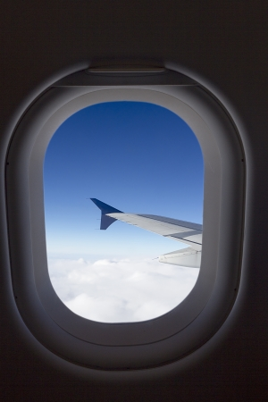 airplane window with wing and cloudy sky behind photo