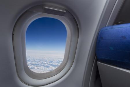 Flugzeug-Fenster mit Flügel und bewölkten Himmel hinter