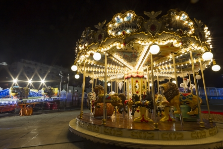 Luna park  in a public outdoor area. Amusement park at night - carousel in motion