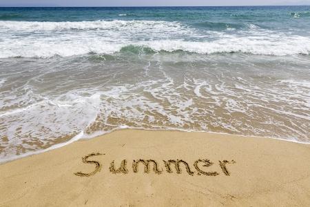 Word-Sommer in Sand am Strand geschrieben