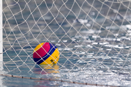 water polo: Salónica, Grecia 05 de marzo 2014: Una pelota de polo acuático flotando en el agua en la red durante el PAOK juego de waterpolo vs Nereas el 5 de marzo de 2014.