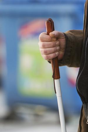 Close up dans les mains de l'homme aveugle tenant un bâton