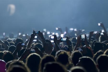 folla: Le persone che assumono le fotografie con touch smartphone durante un intrattenimento musicale concerto pubblico