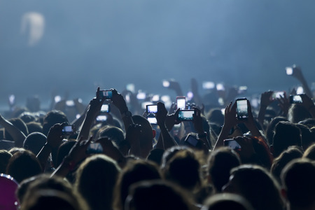 fans: People taking photographs with touch smart phone during a music entertainment public concert  Stock Photo