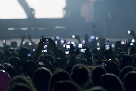 People taking photographs with touch smart phone during a music entertainment public concert  Stock Photo