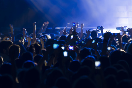 fan dance: People taking photographs with touch smart phone during a music entertainment public concert  Stock Photo