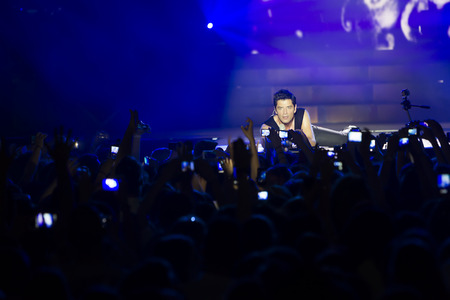 THESSALONIKI, GREECE, MAY 8 2014: Sakis Rouvas engaging with the fans on stage for the Ace of Heart tour at Sports arena in Thessaloniki. Editorial
