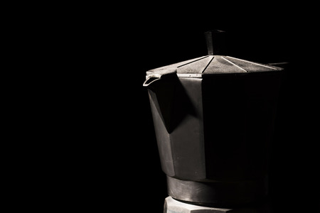 Close up of a typical Italian coffee maker in the shadows in black . photo