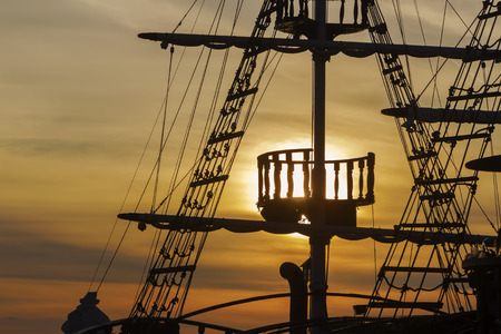 topsail: Silhouette of sails of an antique ship, masts and bowsprit of a schooner at a beautiful sunset, close up. Sepia toned