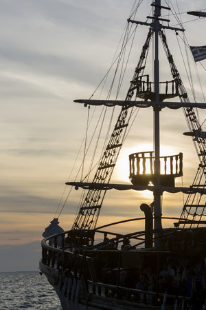 topsail: Silhouette of sails of an antique ship, masts and bowsprit of a schooner at a beautiful sunset, close up.