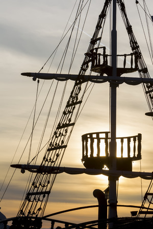 bowsprit: Silhouette of sails of an antique ship, masts and bowsprit of a schooner at a beautiful sunset, close up.