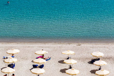 expected: KALLITHEA, GREECE- MAY 27, 2014: Beach with tourists, sun beds and umbrellas. Expected to be the best sea travel destination. Top view of Kallithea, Halkidiki in Greece. .