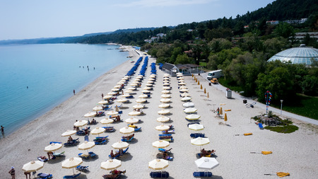 sunbeds: HALKIDIKI, GREECE- MAY 26, 2014: Beach with tourists, sunbeds and umbrellas. Beach of Kallithea, one of the most visited destinations in Greece. Top View Editorial