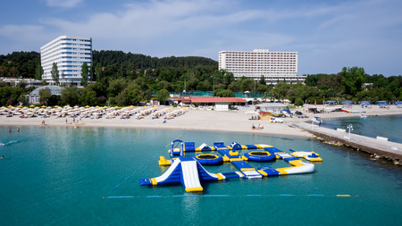 sunbeds: HALKIDIKI, GREECE- MAY 27, 2014: Top view of beach with tourists, sunbeds and umbrellas at a luxury hotel. Sea travel destination in Kallithea, Greece