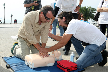 chest compression: THESSALONIKI, GREECE- OCTUBER 16, 2013: People practicing CPR on a mannequin, with the instructors help. Free First Aid, CPR lessons given in the center of Thessaloniki, Greece.