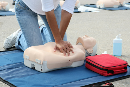Female instructor showing CPR on training doll Standard-Bild