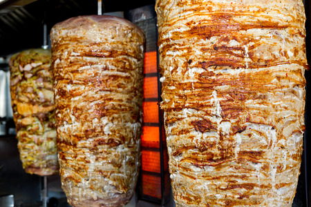 A pair of rotating skewered chicken and lamb meat grilled and ready to serve in a typical Middle Eastern sandwich Standard-Bild