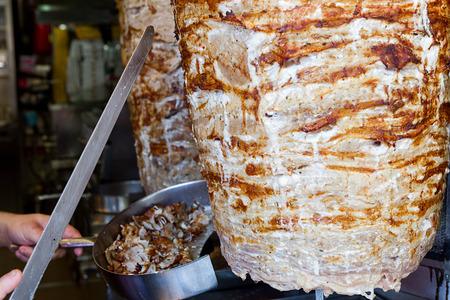 making a sandwich: Shawarma meat being cut before making a sandwich