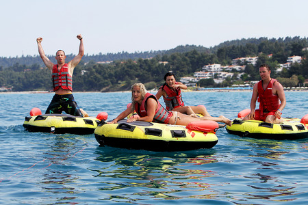 expected: HALKIDIKI, GREECE- MAY 26, 2014: Group of unrecognized people bouncing up over wake on tubes and waving. 20 million tourists expected to visit the beaches, making it a record, in Halkidiki, Greece.    Editorial